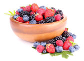 Ripe sweet different berries in wooden bowl, isolated on white — Stock Photo