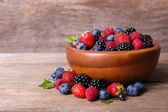 Ripe sweet different berries in bowl, on old wooden table — Stock Photo