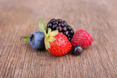 Ripe sweet different berries, on old wooden table — Stock Photo