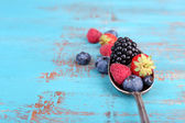 Ripe sweet different berries in vintage spoon, on old wooden table — Stock Photo