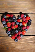 Heart of ripe sweet different berries, on old wooden table — Stock Photo