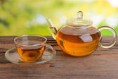 Teapot and cup of tea on table on bright background — Stock Photo