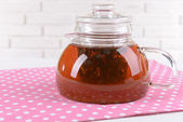 Teapot with tea on table on brick wall background — Stock Photo