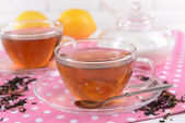 Cups of tea on table on brick wall background — Stock Photo