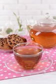 Teapot and cup of tea on table on brick wall background — Stock Photo