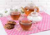Teapot and cups of tea on table on brick wall background — Stock Photo