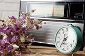 Retro radio with clock and flowers — Stock Photo