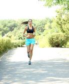 Ung kvinna jogging på park — Stockfoto