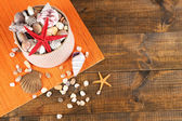 White box full of sea gifts on brown wooden background — Stock Photo