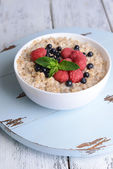 Tasty oatmeal with berries on table close-up — Stockfoto
