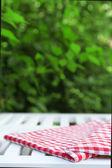 Mesa de madera con mantel, al aire libre — Foto de Stock