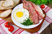 Scrambled eggs with bacon and vegetables served on plate on napkin — Foto Stock