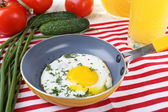 Scrambled egg with vegetables and juice served in pan on a napkin on wooden background — Stock Photo