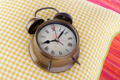 Metal clock on a yellow pillow on red background — Stock Photo