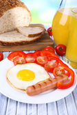Scrambled egg with bread, vegetable and sausage served in plate on wooden background — Stock Photo