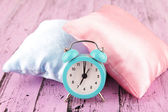 Plastic clock on a silk pillows on wooden background — Stock Photo