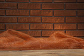 Wooden table with cloth on wall background — Stock Photo
