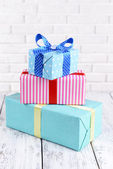 Beautiful gifts on table on brick wall background — Stockfoto