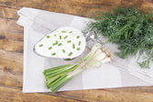 Metal bowl of cream with a tuft of onion, dill and parsley in a basket near it on a napkin on wooden background — 图库照片