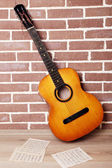 Guitar on the floor on brick wall background — Stockfoto