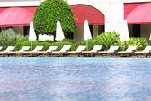 Lounge sunbeds near swimming pool — 图库照片