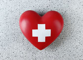 Red heart with cross sign on color background — Stock Photo