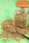 Bay seeds in a glass square bottle with wooden lid on green background — Stock fotografie