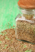Bay seeds in a glass square bottle with wooden lid on green background — ストック写真