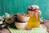Round wooden bowls of seasoning, bay leaves and a glass bottle of honey on a green napkin on a tray on wooden background — Stock Photo