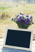 Beautiful wild flowers in vase and empty frame on wooden table on field background — Stock Photo