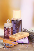 Spa still life with lavender oil and flowers on wooden table, on light background — Stock Photo