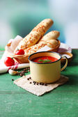Homemade tomato juice in color mug, bread sticks, spices and fresh tomatoes on wooden table, on bright — Stockfoto