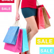 Concept of discount. Female in red shoes holding shopping bags isolated on white — Stock Photo #51650977