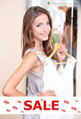 Concept of discount. Beautiful girl trying dress near mirror — Stock Photo