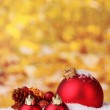 Beautiful red Christmas balls and branch in snow on yellow background — Stok fotoğraf #8115377
