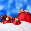 Beautiful blue Christmas balls and branch in snow on blue background — Stockfoto #8115392
