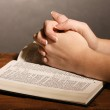 Hands folded in prayer over open russian Holy Bible on black background — Stock Photo #8372146
