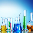 Different laboratory glassware with color liquid and with reflection on blu — Stock Photo #8766284