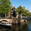Excursion boat in Amsterdam canal — Stok fotoğraf