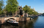 Excursion boat in Amsterdam canal — Stock Photo