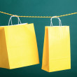 Shopping yellow gift bags on green background — Stock Photo