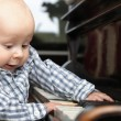 Stock Photo: Beautiful little baby boy plays piano