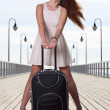 Beautiful woman girl sea mooring suitcase on a pier — Stockfoto