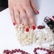 Woman hands a red and white bead — Stock Photo