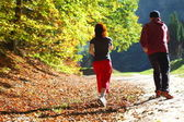 Woman and man walking cross country trail in autumn forest — Stock Photo