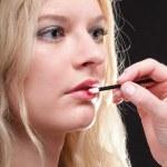 Beautiful woman putting on makeup — Stock Photo #20331941