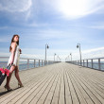 Beautiful woman girl sea mooring suitcase on a pier — Stock Photo