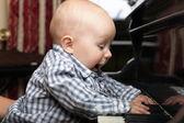 Beautiful little baby boy plays piano — Stock Photo