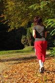 Femme qui marche croix pays sentier dans la forêt d'automne — Photo