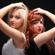 Stock Photo: Two happy young girlfriends black background